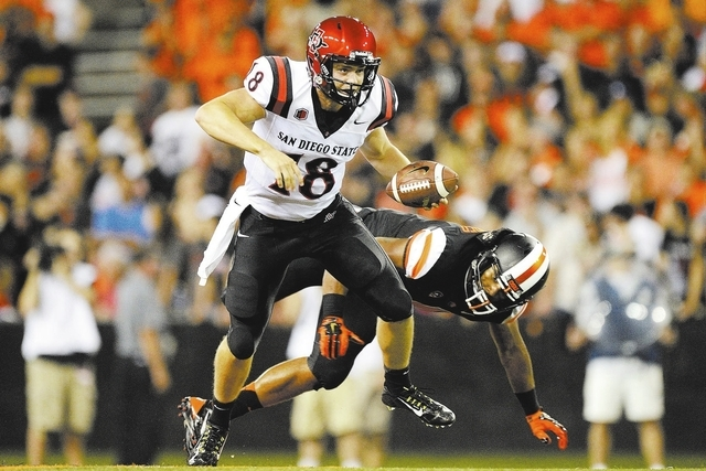 San Diego State quarterback Quinn Kaehler (18) escapes getting tackled by Oregon State defender D.J. Alexander (4) during Saturday's game in Corvallis, Ore. (AP Photo/Troy Wayrynen)