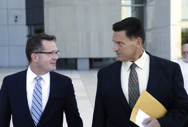 Suspended Las Vegas area family court judge Steven Jones, right, walks out of federal court with his attorney Robert Draskovich Wednesday, Sept. 17, 2014, in Las Vegas.  (AP Photo/John Locher)