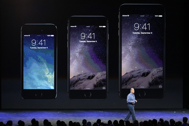 Phil Schiller, Apple's senior vice president of worldwide product marketing, discusses the new iPhone 6, center, and iPhone 6 plus, right, on Tuesday, Sept. 9, 2014, in Cupertino, Calif. (AP Photo ...
