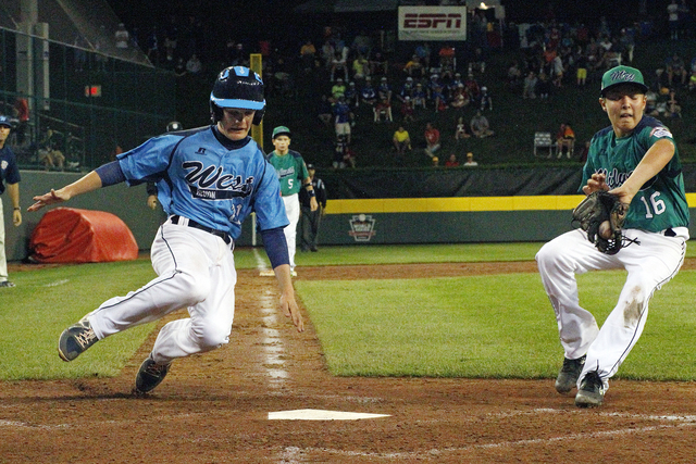 Las Vegas' Austin Kryszczuk, left, scores on a wild pitch by Rapid City, South Dakota pitcher Dylan Richey (16) in the fifth inning of a baseball game in United States pool play at the Little Leag ...
