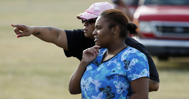 Employees and friends look on for loved ones as police investigate an incident at Vaughn Foods on Thursday, Sept. 25, 2014 in Moore, Oklahoma. Police say a man recently fired from the food process ...