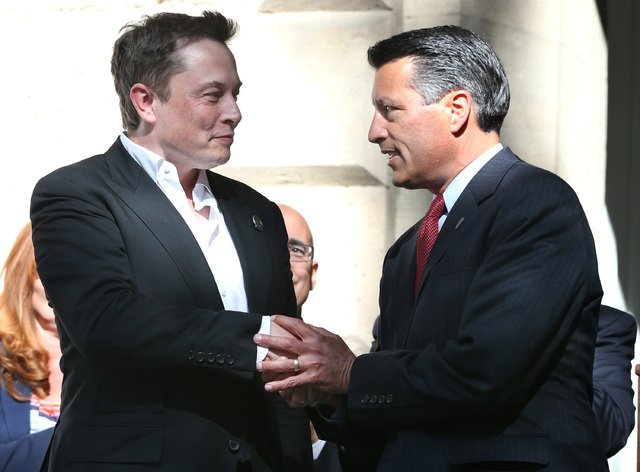 Tesla Motors CEO Elon Musk, left, and Nevada Gov. Brian Sandoval shake hands following a press conference where Nevada was announced as the new site for a $5 billion car battery gigafactory, at th ...