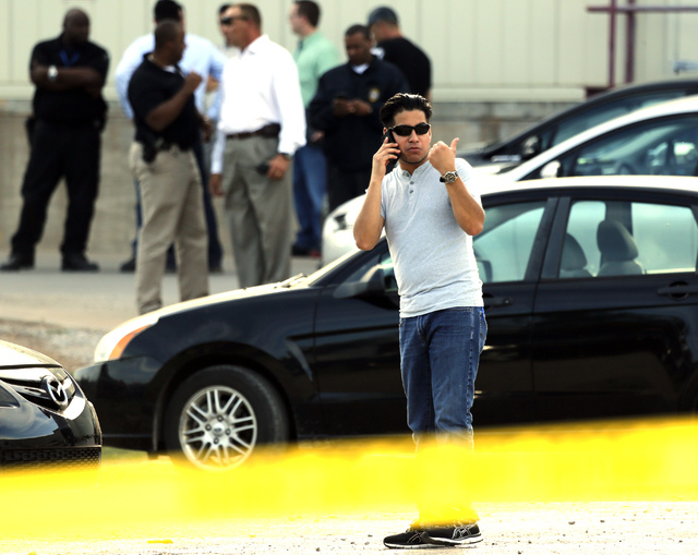 Employees wait in the parking lot as police investigate an incident at Vaughn Foods on Thursday, Sept. 25, 2014, in Moore, Oklahoma. Police say a man recently fired from the food processing plant  ...