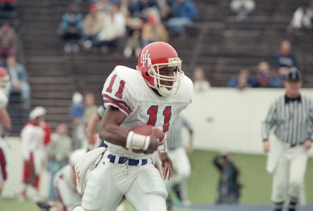 University of Houston Andre Ware runs with the ball during a game against Rice on Dec. 2, 1989. Ware was named the Heisman winner after the game. He was the first black quarterback to win the awar ...