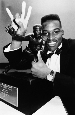 Heisman Trophy winner Andre Ware, from the University of Houston, poses with the trophy in New York, Dec. 7, 1989. (AP Photo/Ira Strickstein)