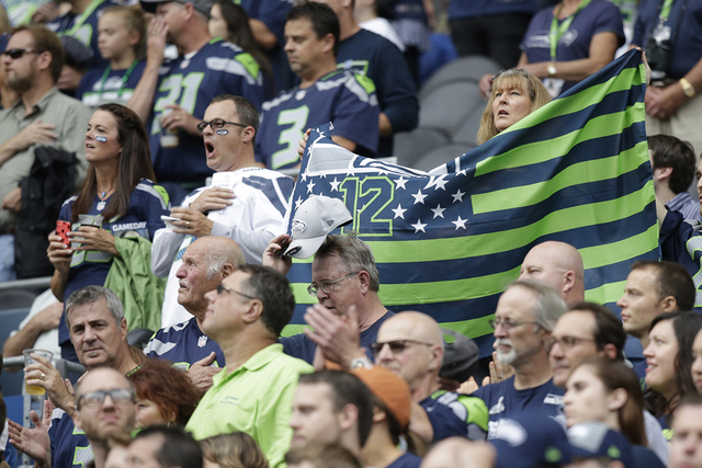 Fans display a Seattle Seahawks flag in the first half of a preseason NFL football game against the San Diego Chargers, Friday, Aug. 15, 2014, in Seattle. (AP Photo/Stephen Brashear)