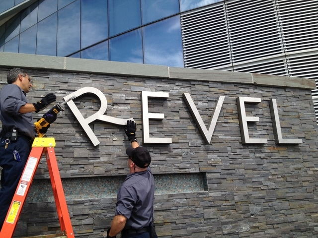 Revel employees Joe Lucchetti, of Turnersville, N.J., left, and Robert Fitting, of Berlin, N.J. remove letters from a sign at Revel hotel-casino, Monday, Sept. 1, 2014, in Atlantic City, N.J. The  ...