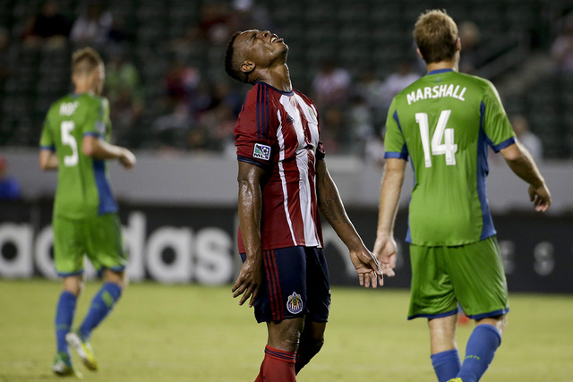 Chivas USA midfielder Carlos Alvarez, middle, reacts after missing a shot as Seattle Sounders midfielder Andy Rose, left, and Chad Marshall walk away during the second half of an MLS soccer match  ...