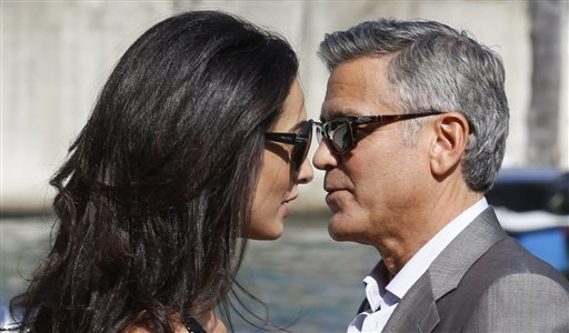 George Clooney, right, and his fiancee Amal Alamuddin arrive in Venice, Italy, Friday, Sept. 26, 2014. Clooney, 53, and Alamuddin, 36, are expected to get married this weekend in Venice, one of th ...