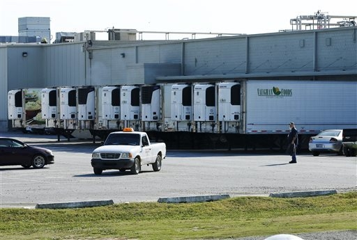 Trucks are parked in a parking lot at Vaughn Foods in Moore, Oklahoma, Friday, Sept. 26, 2014, the site of an incident where a man beheaded a woman with a knife and was attacking another worker wh ...