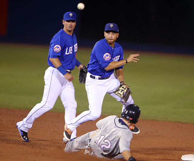 Las Vegas 51s second baseman Anthony Seratelli throws to first as Reno Aces center fielder Michael Freeman is out at second base in the third inning of Game 2 of their PCL Conference Championship  ...