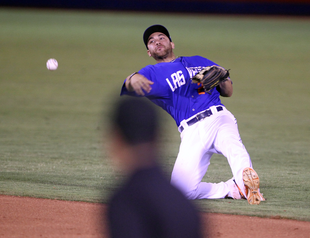 Las Vegas 51s second baseman Anthony Seratelli falls while fielding the ball and tossing it to first base against the Reno Aces in the ninth inning of Game 2 of their PCL Conference Championship S ...