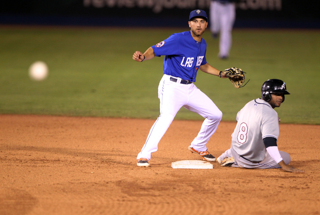 Las Vegas 51s second baseman Anthony Seratelli throws to first to complete a double play as Reno Aces third baseman Andy Marte is out at second base in the sixth inning of Game 1 of their PCL Conf ...