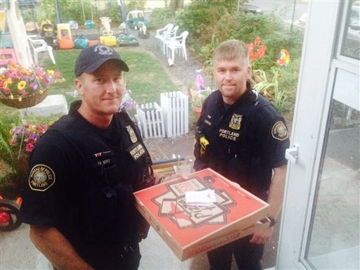 In this photo taken Sept. 1, 2014, and provided by Steve Huckins, Portland police officers Michael Filbert, left, and Royce Curtiss, right, pose after completing a pizza delivery to the Huckins ho ...