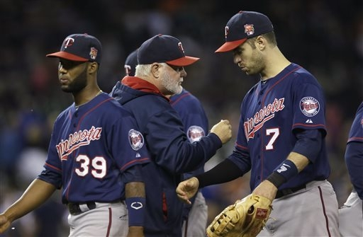 Minnesota Twins manager Ron Gardenhire, center, greets shortstop Danny Santana (39) and first baseman Joe Mauer (7) after their 12-3 win over the Detroit Tigers in a baseball game in Detroit, Satu ...