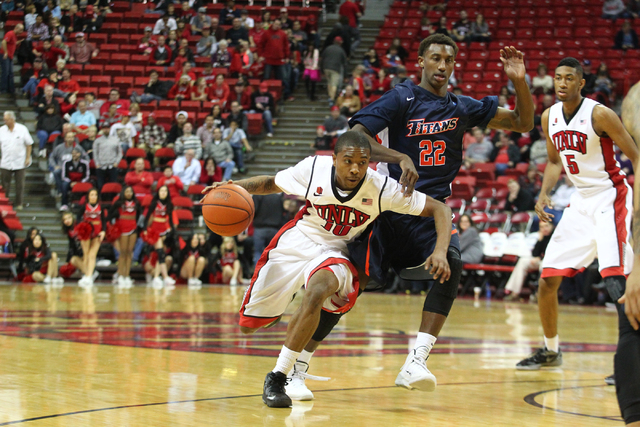 UNLV's Daquan Cook (10) gets past Cal State Fullerton's Sheldon Blackwell (22) during a game at the Thomas & Mack Center in Las Vegas on Saturday, Dec. 28, 2013. UNLV won 83-64 over Cal State Full ...