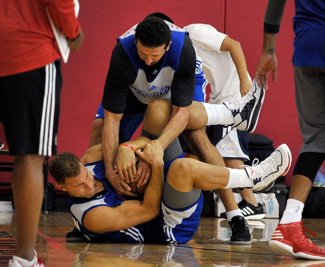 Los Angeles Clippers' Blake Griffin, on ground, wrestles for the ball with teammate Hedo Turkoglu during practice at NBA basketball training camp at the Mendenhall Center at UNLV on Tuesday, Sept. ...