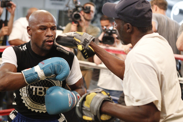 Floyd Mayweather Jr., left, trains with his uncle Roger Mayweather at his gym, Mayweather Boxing Club in Las Vegas, during a media event Tuesday, Sept. 2, 2014. Mayweather hosted the event in anti ...