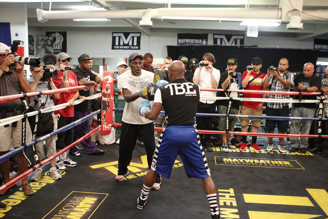Floyd Mayweather Jr., right, trains with his uncle Roger Mayweather at his gym, Mayweather Boxing Club in Las Vegas, during a media event Tuesday, Sept. 2, 2014. Mayweather hosted the event in ant ...