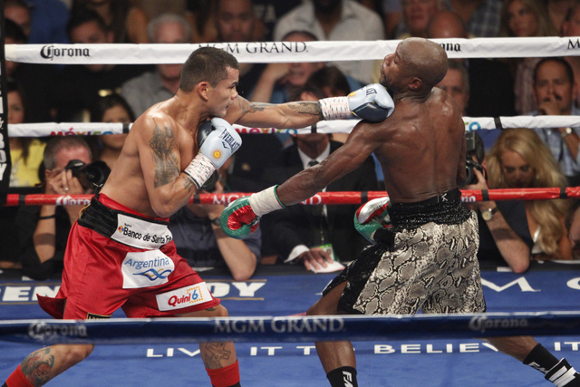 Marcos Maidana, left, connects a punch against Floyd Mayweather Jr. in their boxing bout for the WBC and WBA Welterweight Title and WBC Super Welterweight Title at MGM Grand Garden Arena in Las Ve ...
