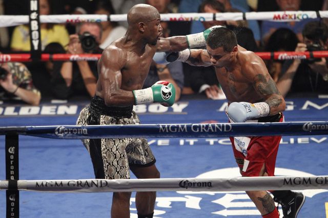 Floyd Mayweather Jr., left, connects a punch against Marcos Maidana in their boxing bout for the WBC and WBA Welterweight Title and WBC Super Welterweight Title at MGM Grand Garden Arena in Las Ve ...