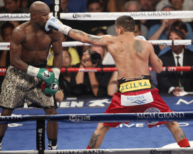Marcos Maidana, right, connects a punch against Floyd Mayweather Jr. in their boxing bout for the WBC and WBA Welterweight Title and WBC Super Welterweight Title at MGM Grand Garden Arena in Las V ...