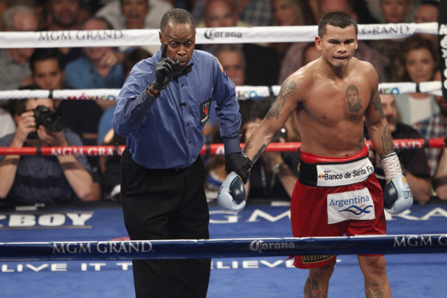 Marcos Maidana, right, is deducted a point for pushing down his opponent Floyd Mayweather Jr. in their boxing bout for the WBC and WBA Welterweight Title and WBC Super Welterweight Title at MGM Gr ...