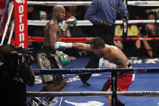 Floyd Mayweather Jr., left, dodges punches against Marcos Maidana in the last round of their boxing bout for the WBC and WBA Welterweight Title and WBC Super Welterweight Title at MGM Grand Garden ...