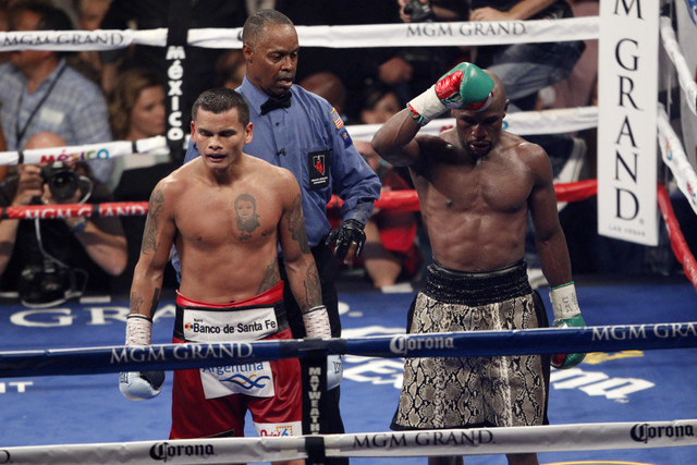 Floyd Mayweather Jr., right, raises his arm in victory at the end of his boxing bout against Marcos Maidana for the WBC and WBA Welterweight Title and WBC Super Welterweight Title at MGM Grand Gar ...