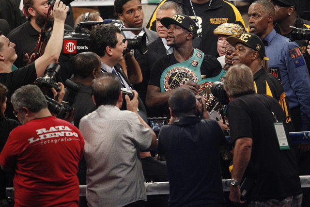 Floyd Mayweather Jr., center, celebrates his boxing victory against Marcos Maidana for the WBC and WBA Welterweight Title and WBC Super Welterweight Title at MGM Grand Garden Arena in Las Vegas Sa ...