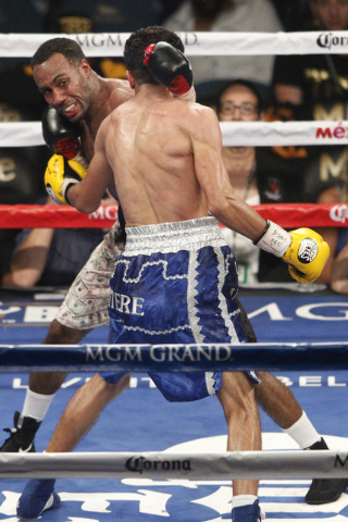 Mickey Bey, left, connects a punch against Miguel Vasquez in their boxing bout for the IBF Lightweight Title at MGM Grand Garden Arena in Las Vegas Saturday, Sept. 13, 2014. Bey won the fight by s ...