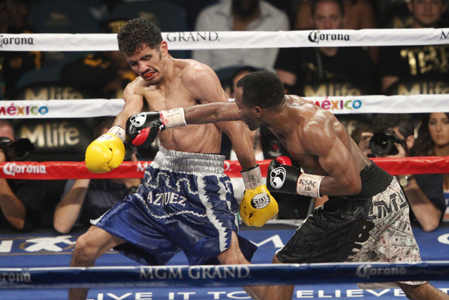Mickey Bey, right, connects a punch against Miguel Vasquez in their boxing bout for the IBF Lightweight Title at MGM Grand Garden Arena in Las Vegas Saturday, Sept. 13, 2014. Bey won the fight by  ...