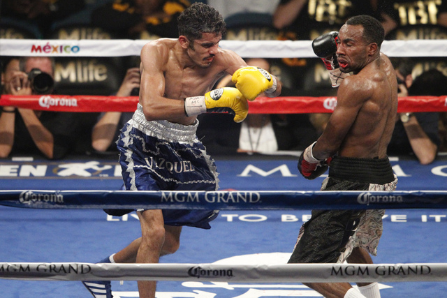 Miguel Vasquez, left, connects a punch against Mickey Bey in their boxing bout for the IBF Lightweight Title at MGM Grand Garden Arena in Las Vegas Saturday, Sept. 13, 2014. Bey won the fight by s ...