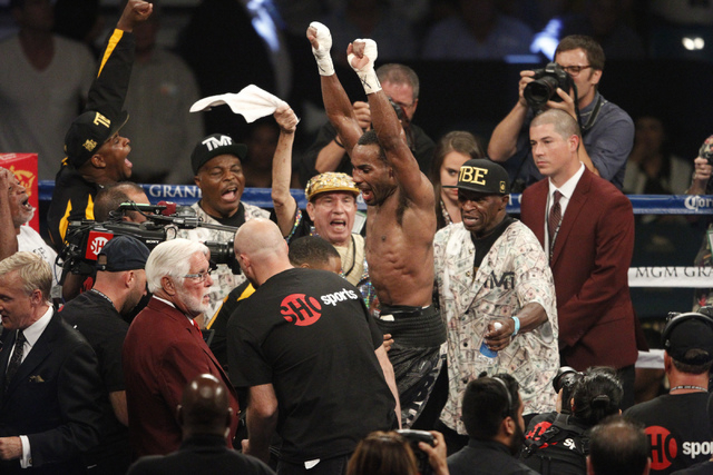Mickey Bey, center, celebrates his victory against Miguel Vasquez in their boxing bout for the IBF Lightweight Title at MGM Grand Garden Arena in Las Vegas Saturday, Sept. 13, 2014. (Erik Verduzco ...