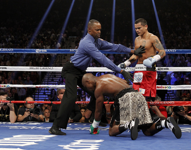 Floyd Mayweather Jr. gets up after falling in the first round against Marcos Maidana during their WBC/WBA welterweight title fight at the MGM Grand Garden Arena in Las Vegas on Saturday, Sept. 13, ...