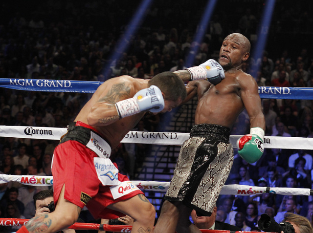 Marcos Maidana connects with Floyd Mayweather Jr. during their WBC/WBA welterweight title fight at the MGM Grand Garden Arena in Las Vegas on Saturday, Sept. 13, 2014. (Sam Morris/Las Vegas Review ...