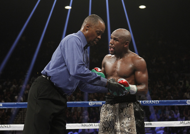 Floyd Mayweather Jr. reacts to referee Kenny Bayless for an incident in the eighth round of his fight with Marcos Maidana during their WBC/WBA welterweight title fight at the MGM Grand Garden Aren ...