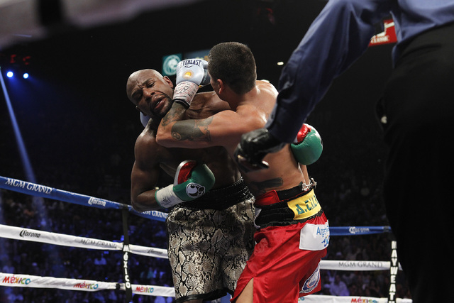 Marcos Maidana puts his forearm to Floyd Mayweather Jr.'s throat during the eleventh round of their WBC/WBA welterweight title fight at the MGM Grand Garden Arena in Las Vegas on Saturday, Sept. 1 ...