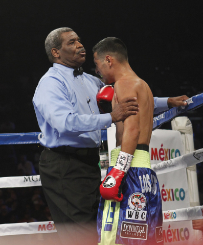 Referee Robert Byrd holds Manuel Roman after Roman was knocked out by Leo Santa Cruz in the second round of their WBC super bantamweight title fight at the MGM Grand Garden Arena in Las Vegas on S ...