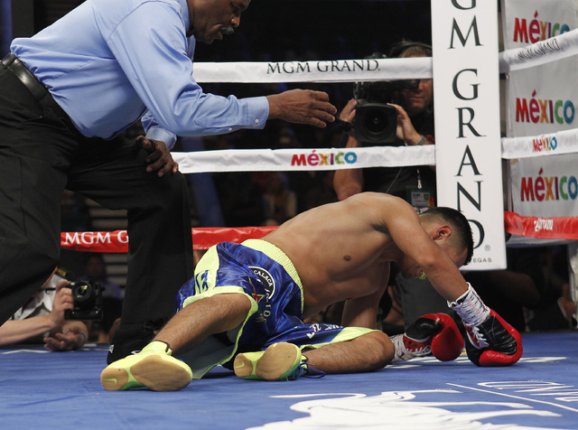Manuel Roman lays on the canvas after being knocked out by Leo Santa Cruz in the second round of their WBC super bantamweight title fight at the MGM Grand Garden Arena in Las Vegas on Saturday, Se ...