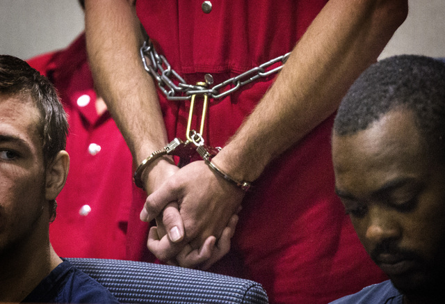 Michael Boyd Jr., 19, in handcuffs, appears  in Henderson Justice Court on Wednesday, Sept. 3, 2014.  He is charged with felonies for putting a barrel of fuel on a bonfire that exploded and led to ...