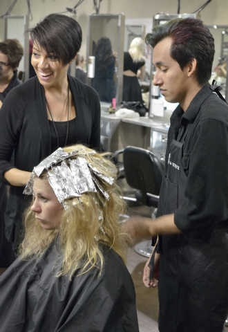 Instructor Deanna Moore, left, helps student Carlos Munoz, right, as he works on highlights for customer Anna Stoeri at the Aveda Institute Las Vegas at 4856 S. Eastern Ave. in Las Vegas on Thursd ...
