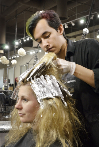 Student Carlos Munoz works on highlights for customer Anna Stoeri at the Aveda Institute Las Vegas at 4856 S. Eastern Ave. in Las Vegas on Thursday, Sept. 11, 2014. (Bill Hughes/Las Vegas Review-J ...