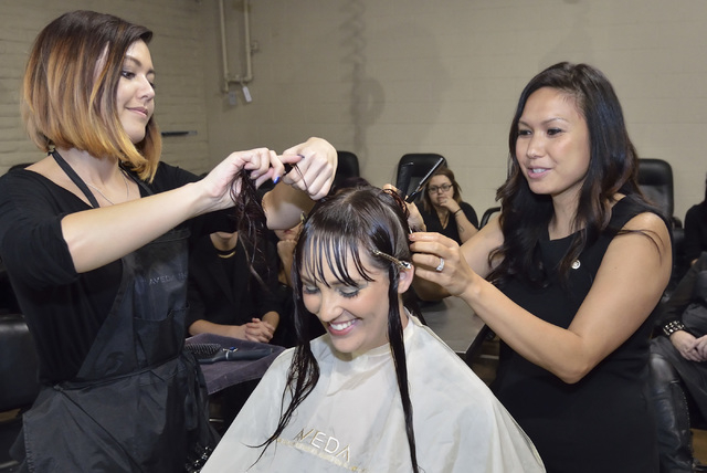 Jessica McMullen, lead instructor at the Aveda Institute Las Vegas, right, gives a haircutting demonstration using Audrea Nuckoles, lead spa educator, center, as a model and student Jessica Tonks  ...