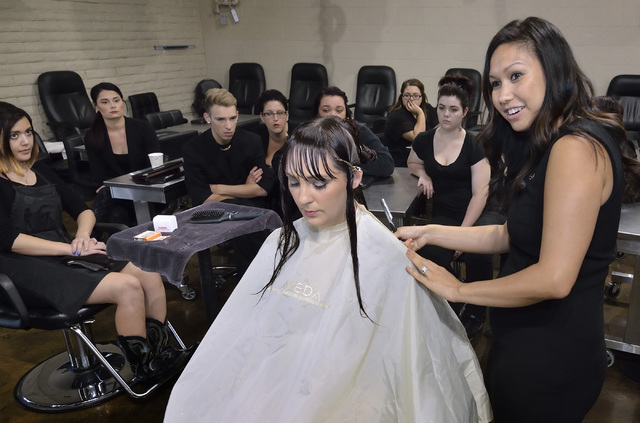 Jessica McMullen, lead instructor at the Aveda Institute Las Vegas, right, gives a haircutting demonstration using Audrea Nuckoles, lead spa educator, as a model in a classroom at the institute at ...