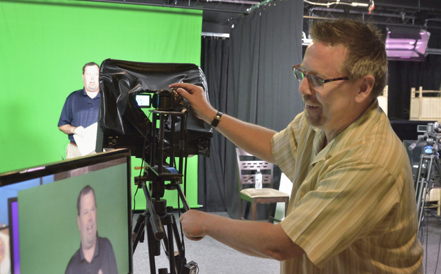 Scott Whitney, founder of the Vegas Video Co-op, right, makes some adjustments before taping a spot for Brett Grant, owner of KSHP AM 1400, background, in the co-op studio at 101 Convention Center ...