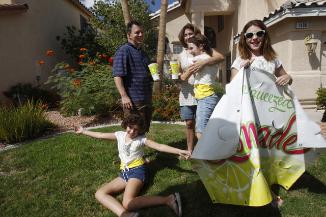 Rock Rocheleau, clockwise from back left, his wife Stacy, and daughters Jordan, 12, Jenna 12, and Stacy, 10, pose for a portrait with their lemonade sign at their home in Henderson Saturday, Sept. ...