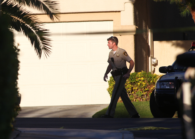 A Las Vegas police officer walks along the 1600 block of Broadmere Street on Monday, Sept. 22, 2014, where a fatal shooting occurred about 10 p.m. Sunday, Sept. 21, near Hualapai Way and Charlesto ...