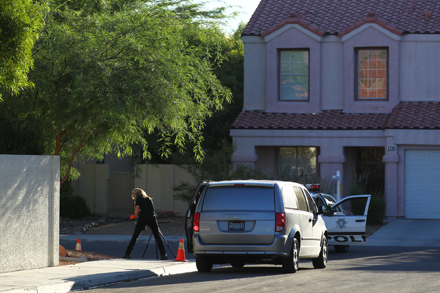 A crime scene investigator is seen at the intersection of Shifting Winds Street and Ranch Hand Avenue on Monday, Sept. 22, 2014, near the 1600 block of Broadmere Street where a fatal shooting occu ...