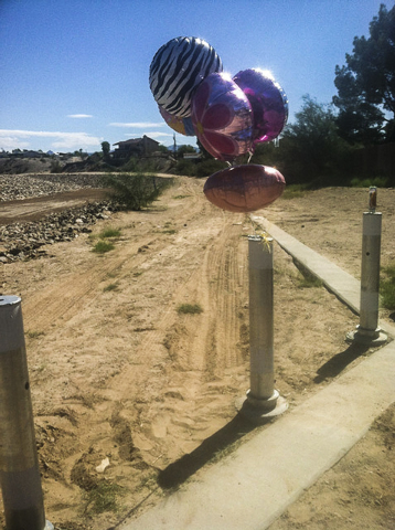 Balloons were left near the lot at Chaparral and Country Club drives in Bullhead City, Arizona, where the body believed to be 8-year-old Isabella Grogan-Cannella was found Wednesday. (Annalise Lit ...